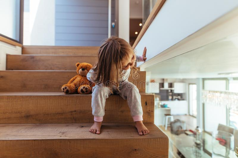 Little girl sitting on staircase at home stock image