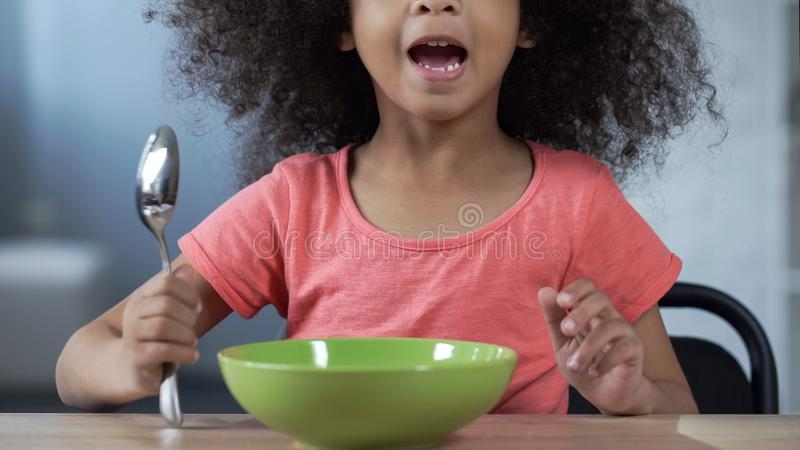 Cute little girl sitting at table with spoon and asking for dinner, hungry kid stock photography