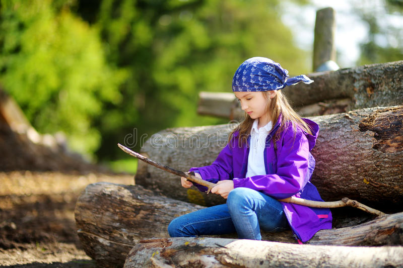 Cute little girl sitting on tree logs using a pocket knife to whittle a hiking stick stock photography