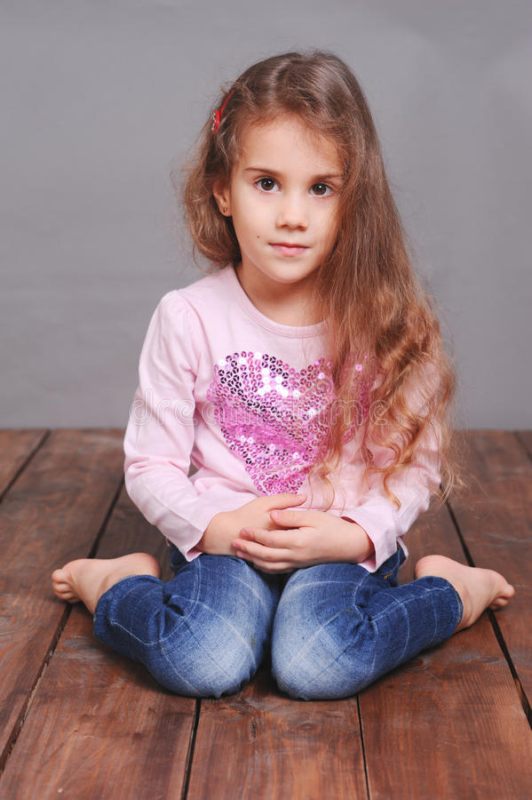 Cute little girl sitting on wooden floor royalty free stock photography