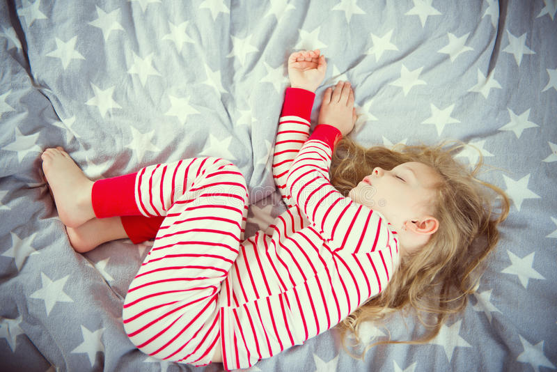 Cute little girl sleeps in pajames on bed royalty free stock photography