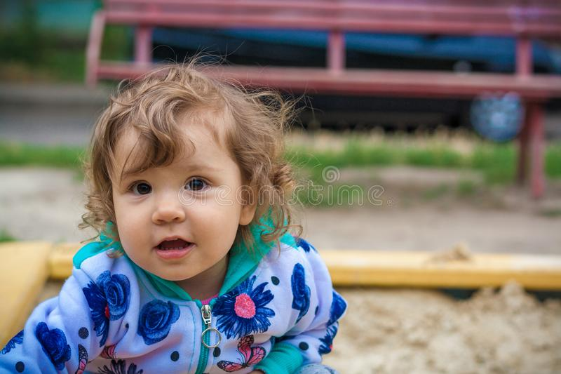 Cute little girl smiling playing in the sandbox royalty free stock photography