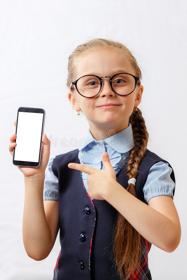 Happy little girl show her smartphone with white screen. mockup royalty free stock photo