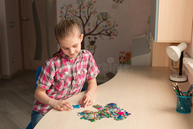 Cute little girl solving puzzle together royalty free stock photography