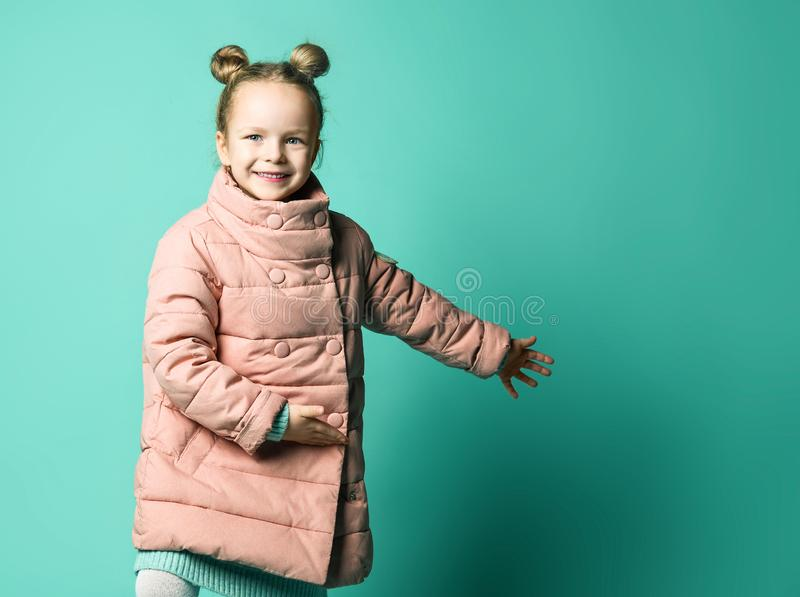Cute little girl in a spring coat points with two palms of her hands to the side to free space. stock photo