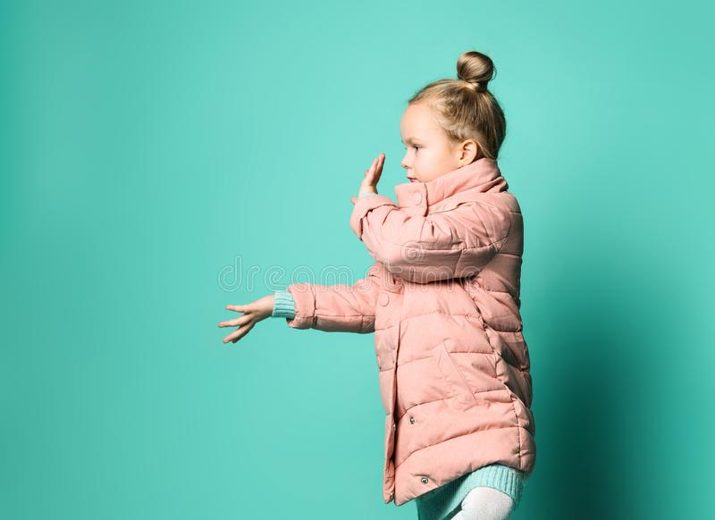 Cute little girl in a spring coat points with two palms of her hands to the side to free space. royalty free stock image