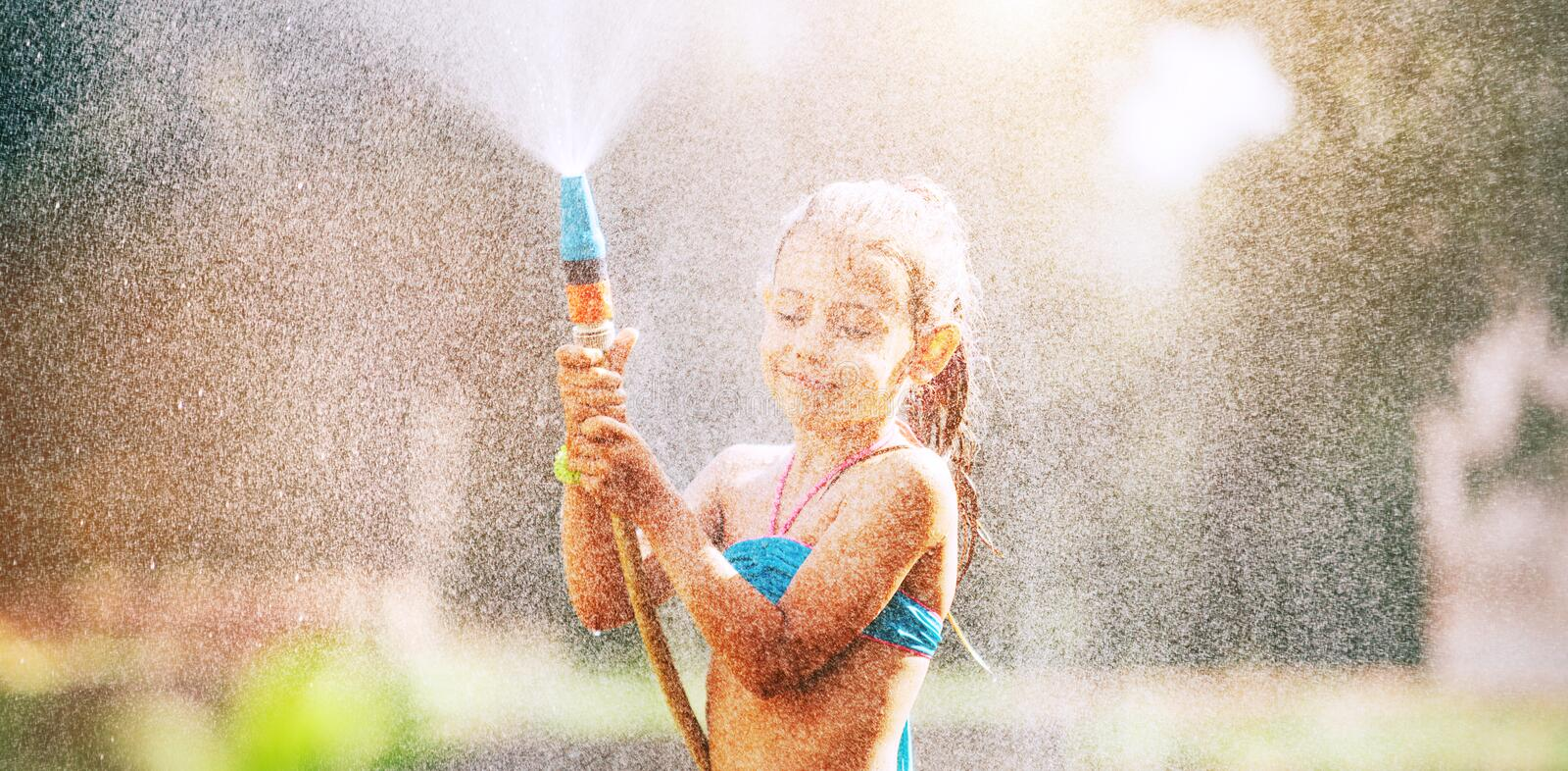 Cute little girl sprinkls a water for herself from the hose, makes a rain. pleasure for hot summer days stock image