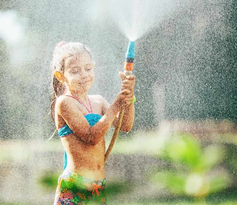 Cute little girl sprinkls a water for herself from the hose, makes a rain. pleasure for hot summer days royalty free stock photo