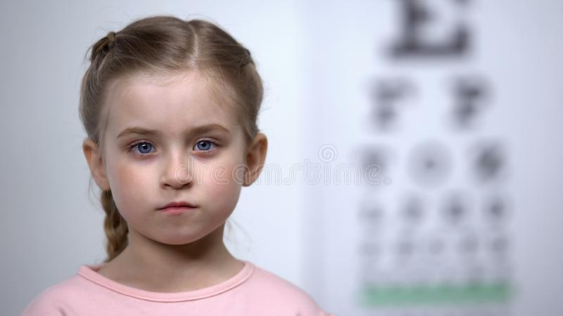 Cute little girl standing on background of visual acuity testing table, optics royalty free stock photography