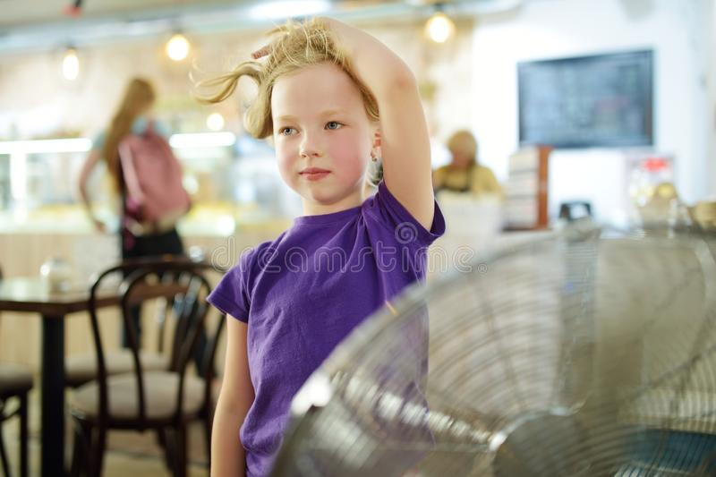 Cute little girl standing in front of a fan on hot summer day. Child enjoying cool wind in summer season royalty free stock photography