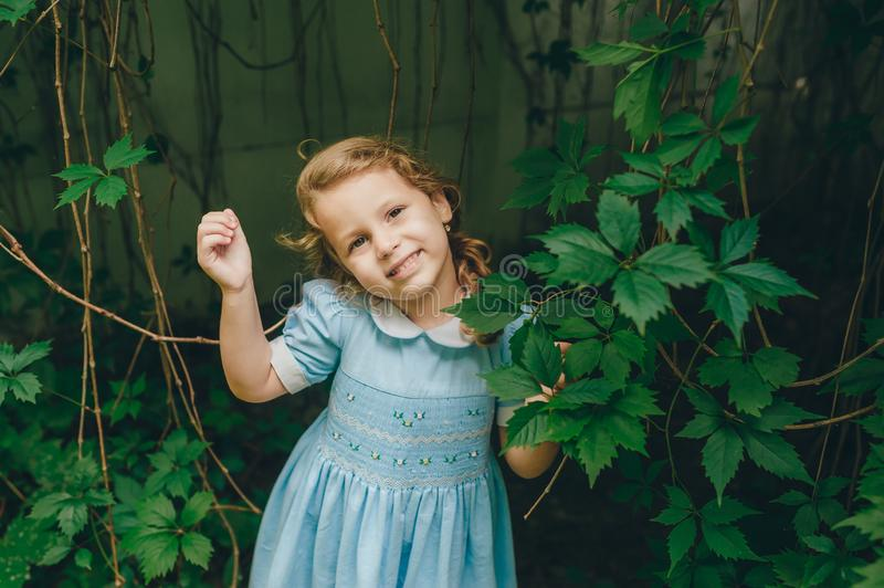 Cute little girl is standing in garden between green leaves of grapes and she looking to camera. Attractive face and beautiful eyes expression. Concept of royalty free stock image