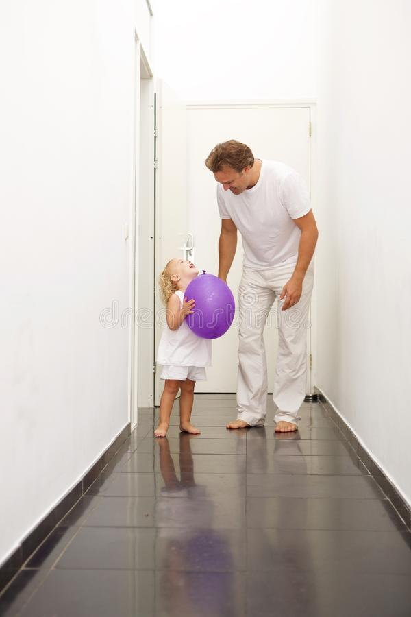 Cute little girl standing with her father at home royalty free stock image