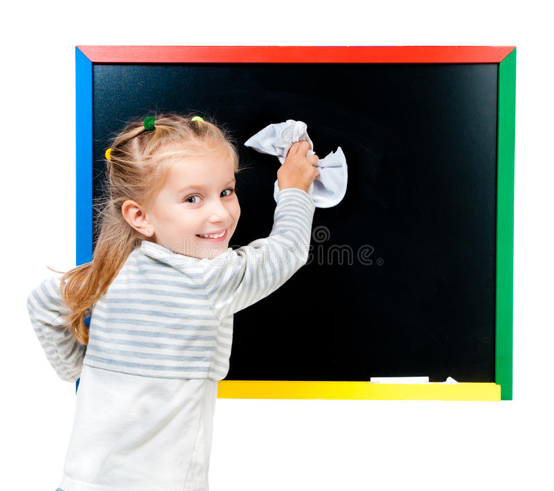 Cute little girl standing near blackboard. Isolated on white royalty free stock image