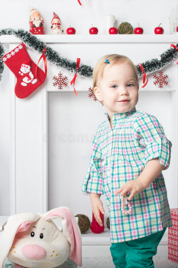 Cute little girl standing near New Year Christmas fireplace stock images