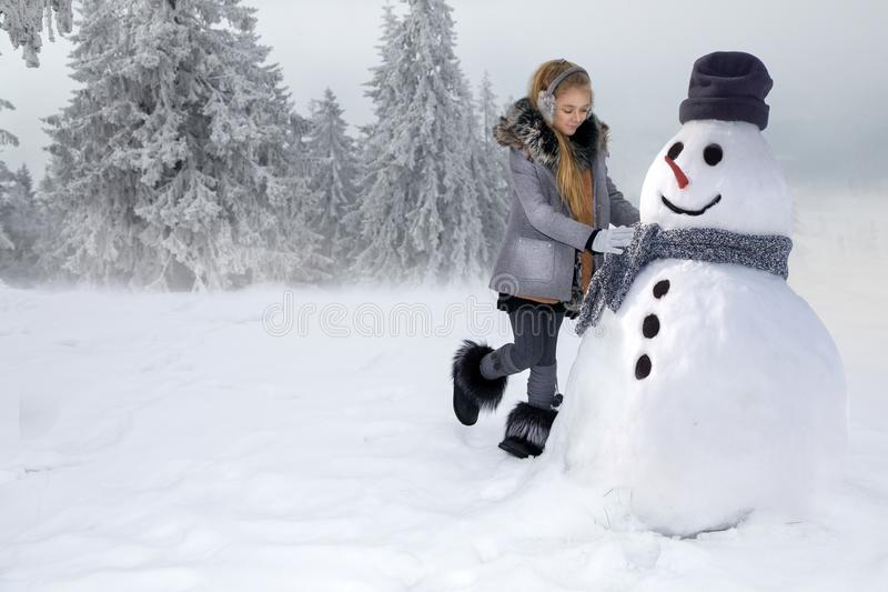 Cute little girl, standing on the snow and makes a snowman with snow. The girl is dressed in winter clothing. royalty free stock photos