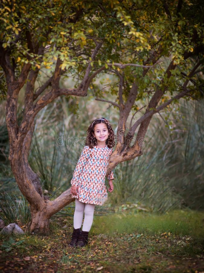 Little girl is standing by the tree stock photography