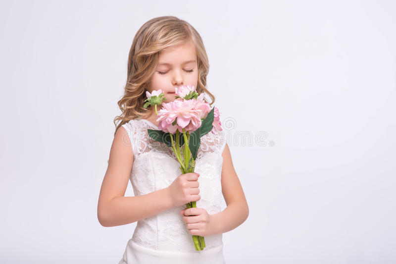 Cute little girl standing in a wedding dress. Unforgettable scent. Cute beautiful little girl holding bouquet of flower while feeling the aroma royalty free stock photos