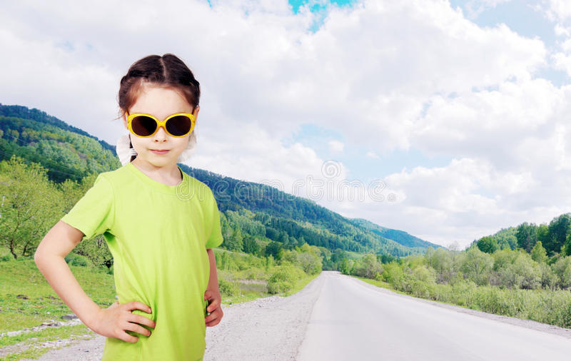 Cute little girl stands on the roadside. Cute little girl wearing sunglasses stands on the roadside stock images
