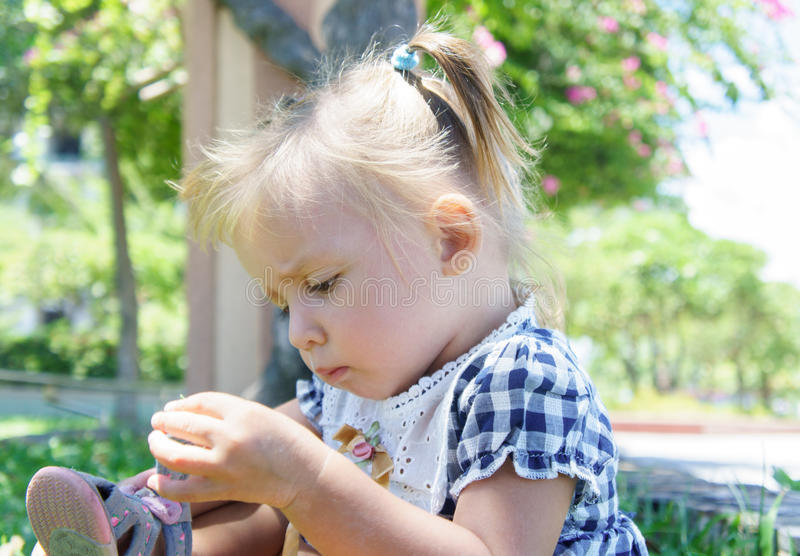 Cute little girl with straight face in summer day. mending sandals. stock photo