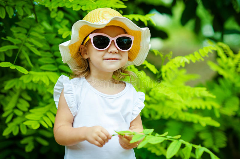 Cute little girl In a straw hat and pink sunglasses is playing with leaves in summer park stock image