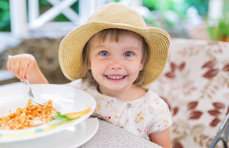 Cute little girl in straw hat sit at table and eating tasty dish from white plate. stock photo