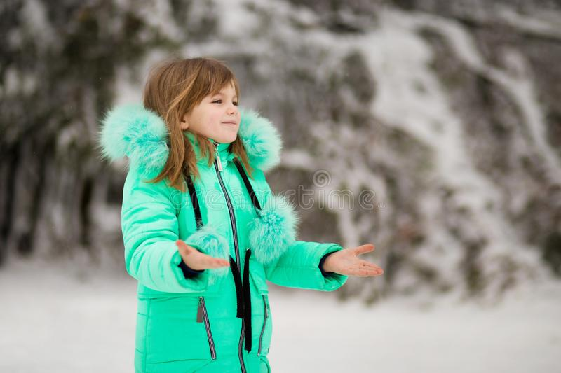 Cute little girl stretches her hand to catch falling snowflakes. royalty free stock photos