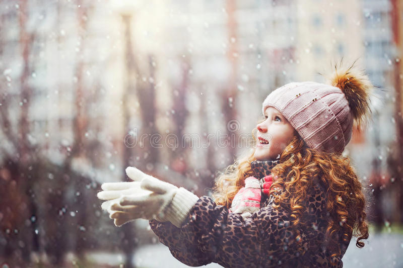 Cute little girl stretches her hand to catch falling snowflakes. royalty free stock photo