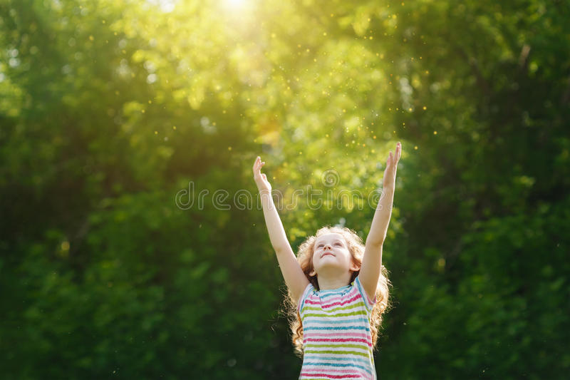 Cute little girl stretches her hand to catch sun rays. royalty free stock photo