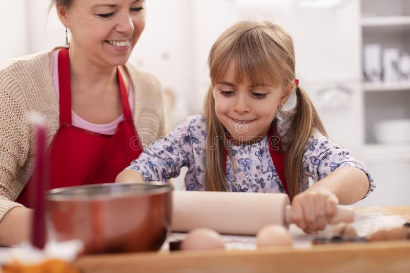 Cute little girl stretching the cookie dough - her mother supervising the operation stock photography