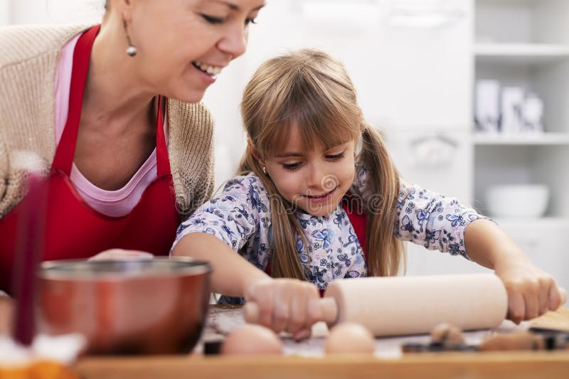 Cute little girl stretching the cookie dough at the kitchen table with her mother royalty free stock photography