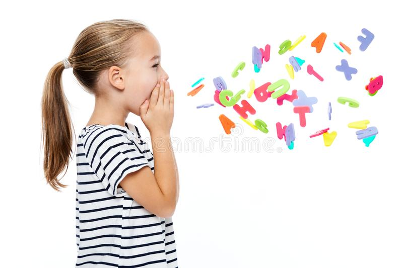 Cute little girl in stripped T-shirt shouting out alphabet letters. Speech therapy concept over white background. stock image