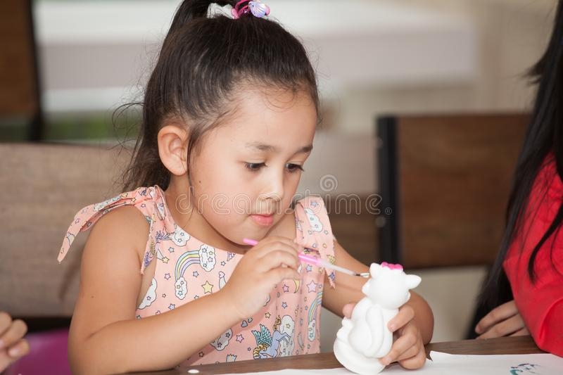 Cute little girl student painting a ceramic pottery model  in classroom school . kid artist . child sitting at desk preschool . royalty free stock images