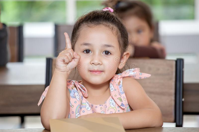 Cute little girl student pointing finger up in classroom school . Genius kid. Great idea . child clever sitting at desk preschool stock images