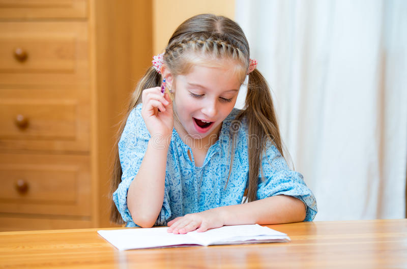 Cute little girl studying. At home and smiling stock photo