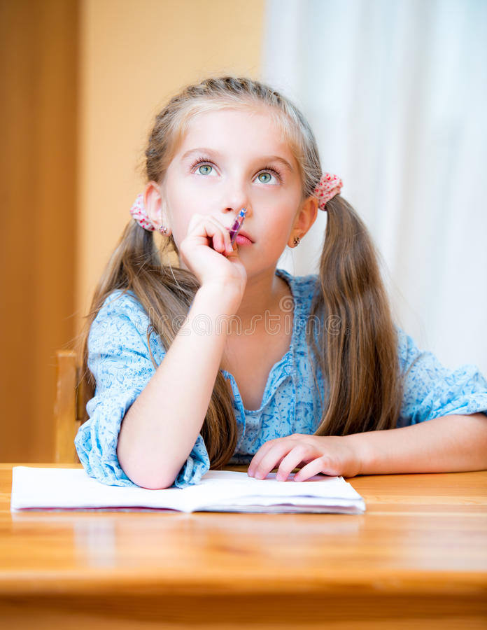 Cute little girl studying. Cute pensive little girl studying at home and smiling stock images