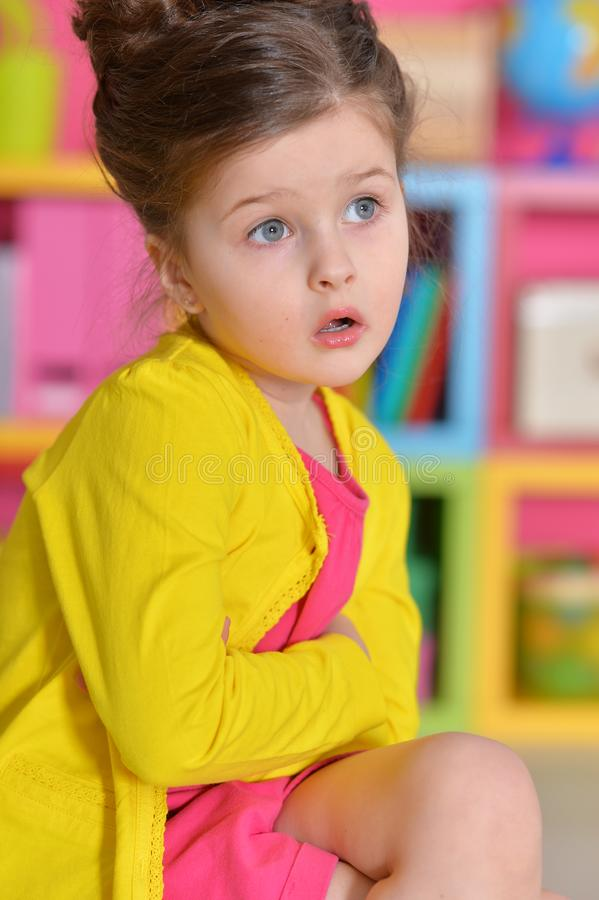 Portrait of cute little girl with stylish hairstyle wearing yellow jacket posing stock photography