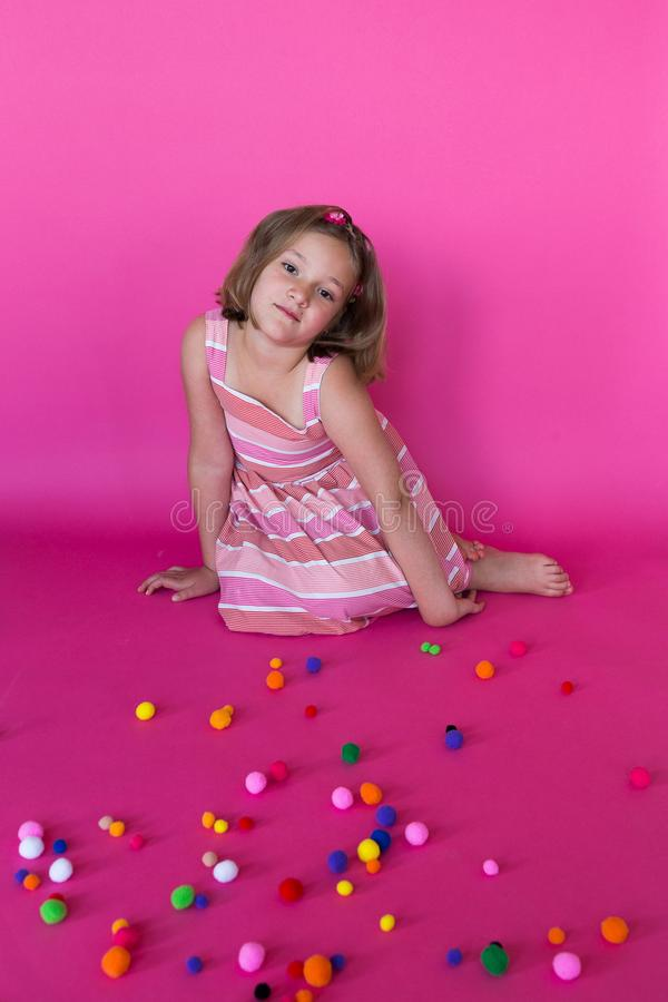 Cute little girl in summer dress sitting behind scattered colorful pompoms royalty free stock images
