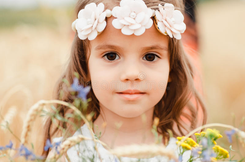 Cute little girl in the summer field of wheat. A child with a bouquet of wildflowers in his hands. Close up, Portrait stock photography