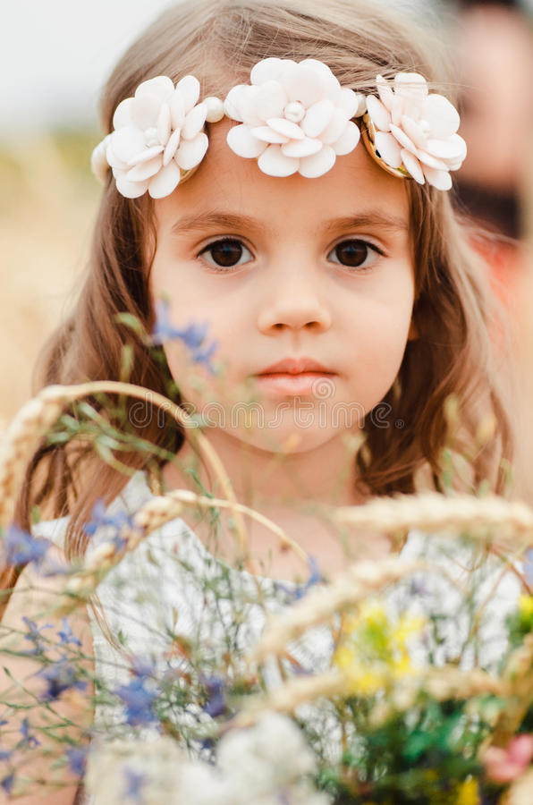 Cute little girl in the summer field of wheat. A child with a bouquet of wildflowers in his hands. Close up, Portrait.  royalty free stock photography