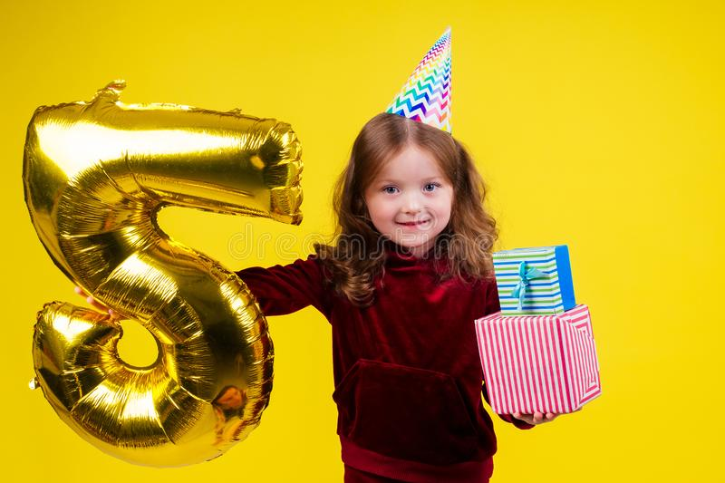 Cute little girl surprised and amazed with birthday cap horn holding ballons 5 years anniversary numeral and gift box in. Studio white background stock photography