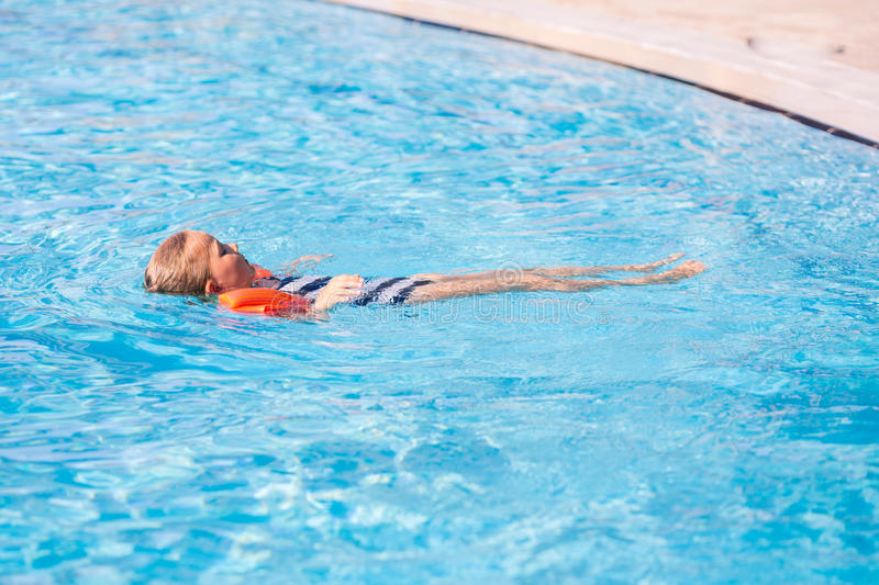 Cute little girl in swimming pool in armbans. Learning how to swim royalty free stock photo