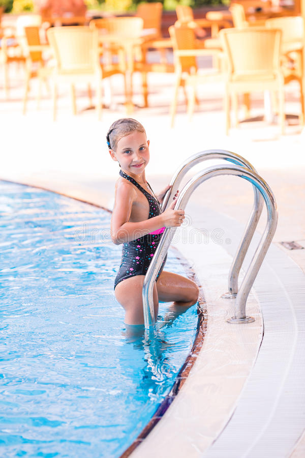 Cute little girl in swimming pool. Cute little girl getting out of swimming pool stock photo