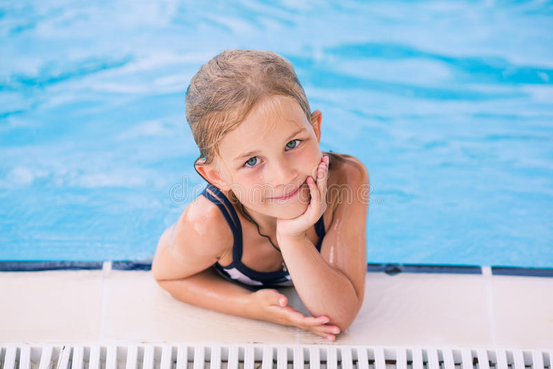 Cute little girl in swimming pool. Learning how to swim stock photo