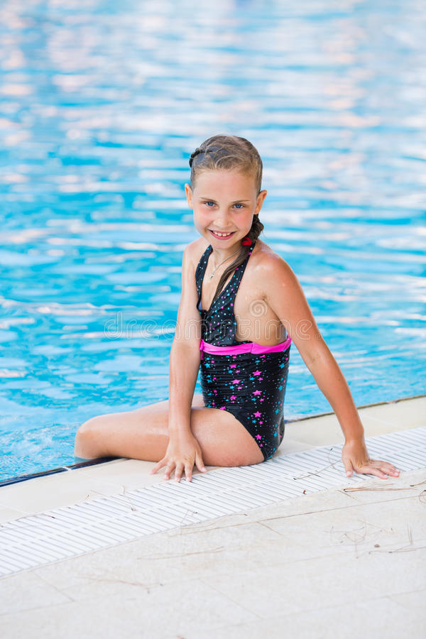 Cute little girl in swimming pool. Learning how to swim stock photos
