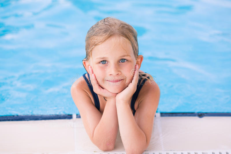 Cute little girl in swimming pool. Learning how to swim royalty free stock photography