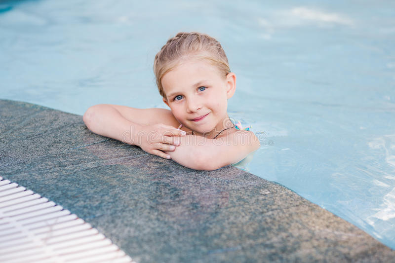 Cute little girl in swimming pool. Learning how to swim royalty free stock photos