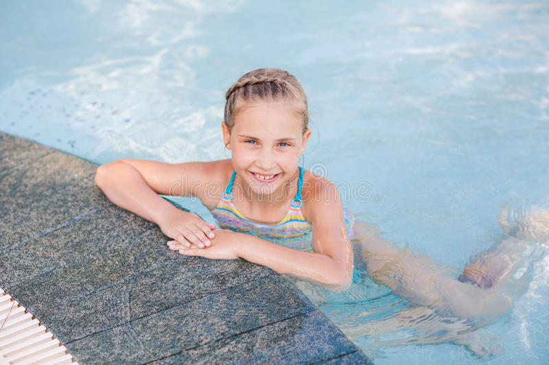 Cute little girl in swimming pool. Learning how to swim stock photography
