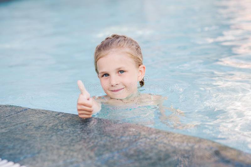 Cute little girl in swimming pool. With thumb up royalty free stock photos