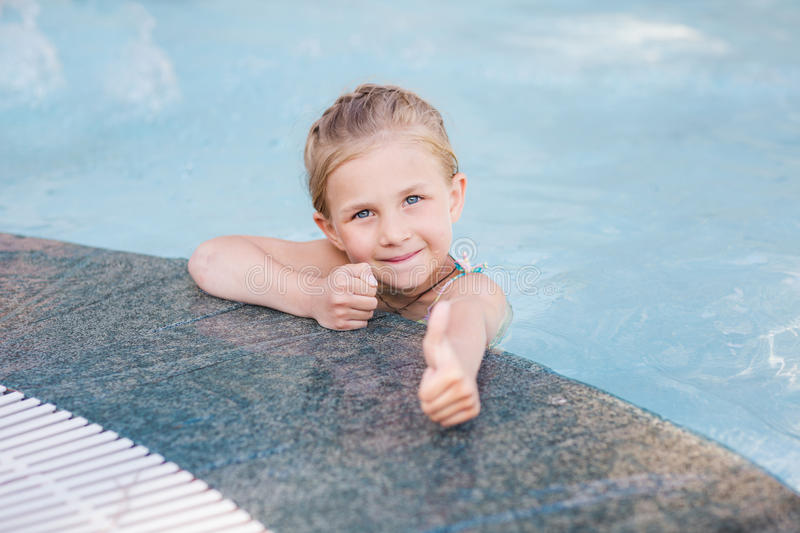 Cute little girl in swimming pool. With thumb up stock photos