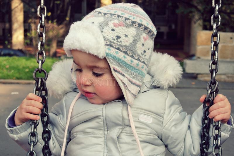 Cute little girl on the swing in winter; retro Instagram style stock images